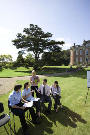 lavishly: Businessmen and women on chairs on grass by manor house, in training course, elevated view