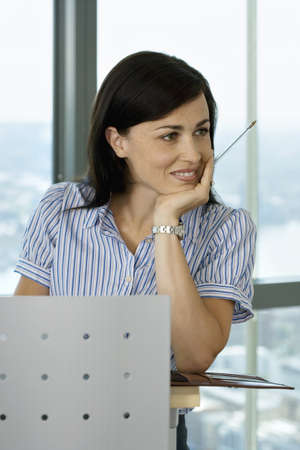 toils: Businesswoman leaning on lectern beside window in conference room, hand on chin, smiling, close-up