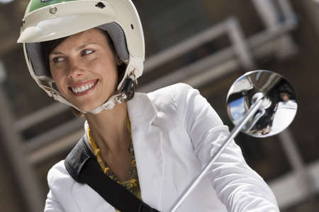 sitt: Woman in crash helmet riding on scooter in street, smiling, front view, close-up (tilt)