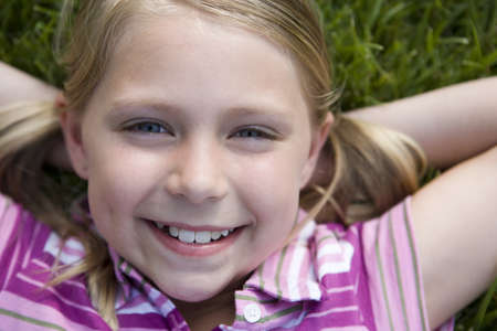 fem: Girl (8-10) lying on grass, hands behind head, smiling, close-up, portrait, overhead view