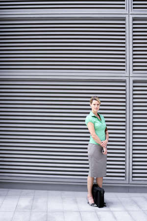gals: Businesswoman in green short-sleeved blouse and grey skirt standing on pavement, portrait