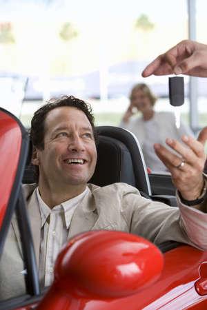 lavishly: Salesman handing key to satisfied male customer sitting in red convertible in car showroom, smiling