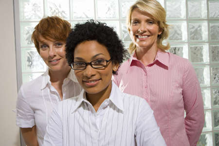 toils: Three businesswomen standing by glass block wall, smiling, portrait, close-up