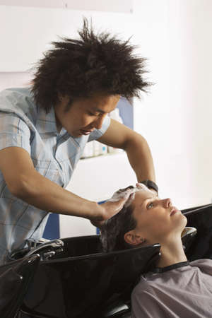shampooing: Young male hairdresser shampooing womans hair in salon, side view LANG_EVOIMAGES