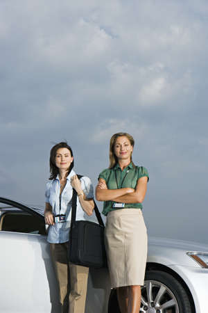 toils: Two businesswomen standing beside car, smiling, portrait