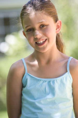 waistup: Girl (8-10) en el chaleco de color turquesa de pie en el jard�n de verano, sonriendo, vista frontal, retrato