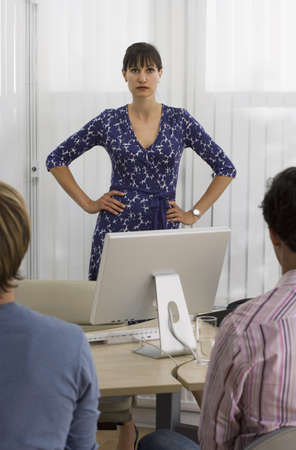 toils: Businesswoman talking to male colleagues behind desk in office, hand on hips, portrait