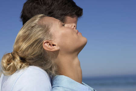 leant: Couple standing on beach, man embracing woman, smiling, eyes closed, close-up, profile