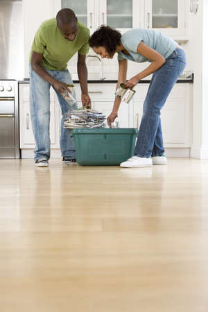 bundling: Young couple putting glass jars, cans and newspapers into recycling bin in kitchen, low angle view LANG_EVOIMAGES