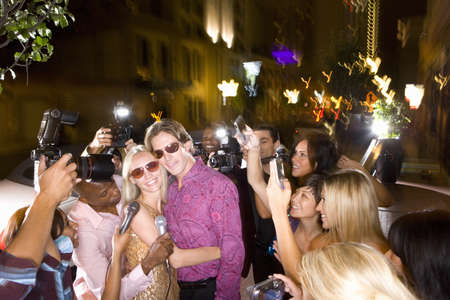 lavishly: Young couple arm in arm surrounded in paparazzi, smiling