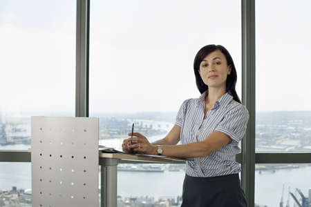 lectern: England, London, Canary Wharf, businesswoman standing behind lectern, giving presentation