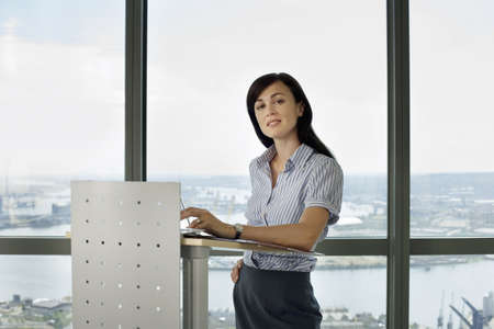 toils: England, London, Canary Wharf, businesswoman standing behind lectern, giving presentation