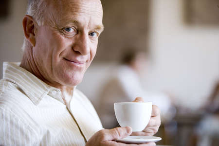 peo: Senior man drinking cup of coffee in café, smiling, close-up, side view, portrait