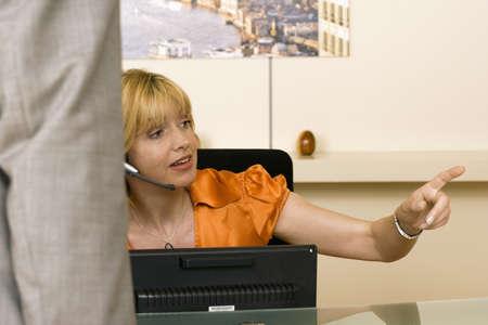 fema: Receptionist working behind reception desk, showing businessman the way, pointing finger