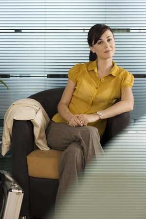 western european ethnicity: Confident businesswoman in yellow short-sleeved blouse sitting in office chair, portrait LANG_EVOIMAGES