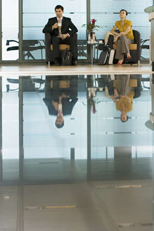 western european ethnicity: Businessman and businesswoman sitting in lobby, man holding cup, reflection on shiny floor