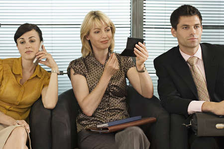 western european ethnicity: Business people waiting in office reception, woman using mobile phone, second woman applying make-up