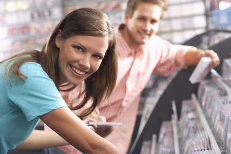 bending down: Mujer joven que pasa de CD para hombre en tienda de discos, inclin�ndose hacia abajo, sonriendo, vista lateral, retrato, se centran en primer plano