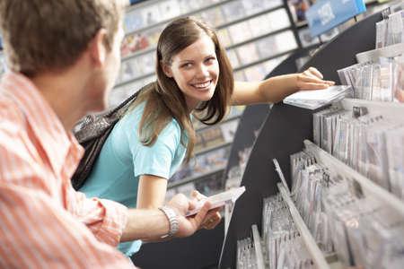 bending down: Hombre joven que pasa de CD a la mujer en la tienda de discos, inclin�ndose hacia abajo, sonriendo, vista lateral, centrarse en segundo plano (inclinaci�n)