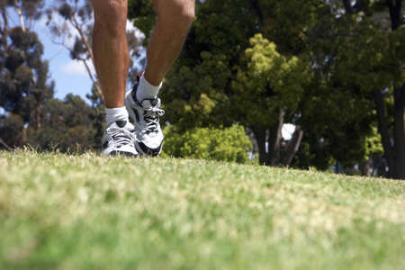 nat: Man jogging on grass in park, low section, surface level, focus on trainers LANG_EVOIMAGES