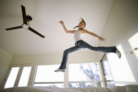 fan ceiling: Girl (11-13) jumping up and down on bed, mirroring shape of electric ceiling fan, smiling, portrait, low angle view LANG_EVOIMAGES