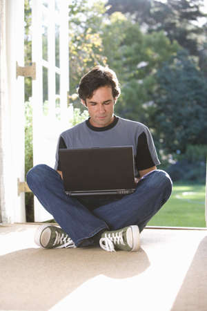french doors: Man sitting on floor by French doors, legs crossed, laptop on lap
