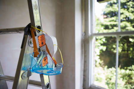 sunshines: Protective safety goggles and dust mask hanging from step ladder in room beside window