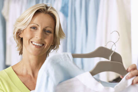 coathangers: Mature woman shopping in clothes shop, holding two tops on coathangers, smiling, close-up, portrait