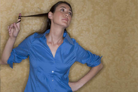 waistup: Young businesswoman with hand on hip playing with hair