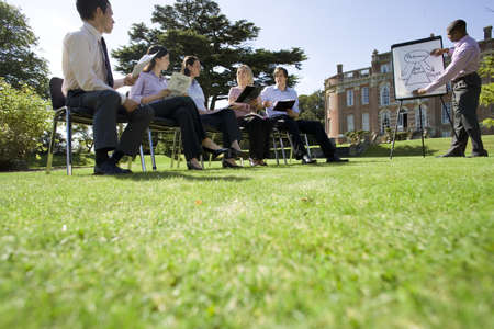 lavishly: Businessmen and women with folders in training course by manor house, ground view