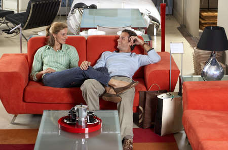 furniture store: Couple testing new red sofa in furniture store, woman sitting with feet up on mans lap, smiling LANG_EVOIMAGES