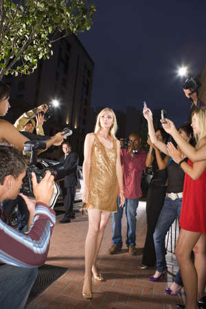lavishly: Young woman surrounded in people taking photographs, low angle view LANG_EVOIMAGES