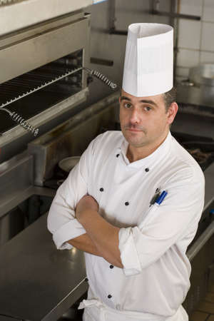elevated view: Male chef standing in commercial kitchen, arms folded, portrait, elevated view