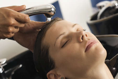 toils: Hairdresser rinsing womans hair in salon, customer with eyes closed, close-up LANG_EVOIMAGES