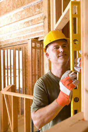 toiling: Builder in hardhat using spirit level