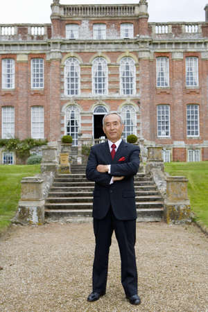 lavishly: Mature businessman with arms crossed in front of manor house, portrait