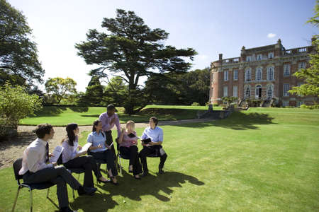 lavishly: Businessmen and women with folders in grounds by manor house