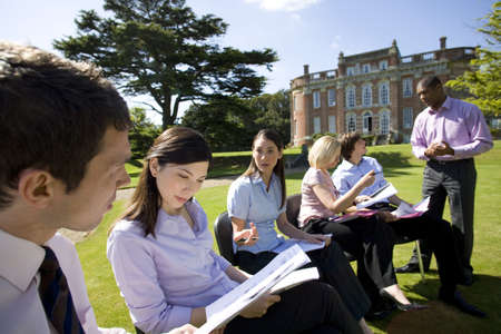 western european ethnicity: Businessmen and women with folders in grounds by manor house