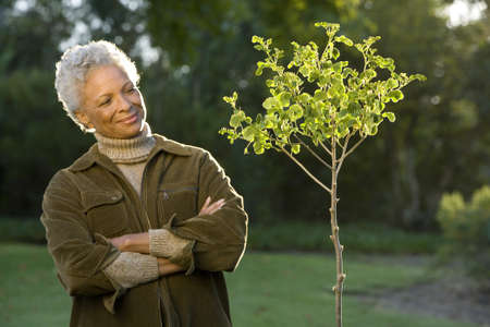 gratifying: Senior woman standing beside small tree in autumn garden, arms folded, smiling, portrait