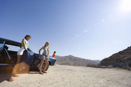 western european ethnicity: Small group of friends by car in desert, looking at view, low angle view (lens flare) LANG_EVOIMAGES