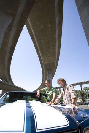 waistup: Dos j�venes en coche por debajo de puente, sonriente, retrato, vista de �ngulo bajo LANG_EVOIMAGES