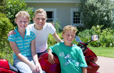 waistup: Mother and children (8-10) standing beside motorbike on driveway, smiling, portrait LANG_EVOIMAGES