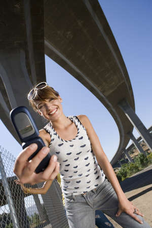 appreciating: Young woman taking photograph beneath overpasses, smiling, portrait, low angle view LANG_EVOIMAGES