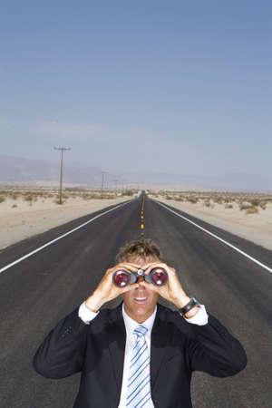waistup: Businessman in middle of open road in desert, using binoculars, elevated view