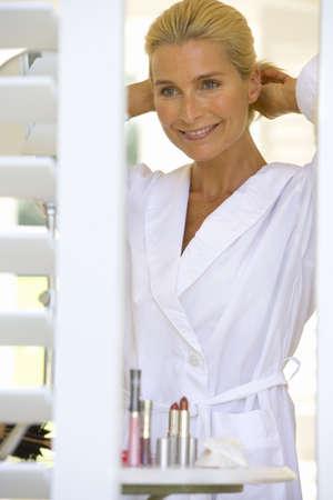 waistup: Mujer madura en albornoz que ajusta el pelo, sonriendo, vista a trav�s de persianas LANG_EVOIMAGES