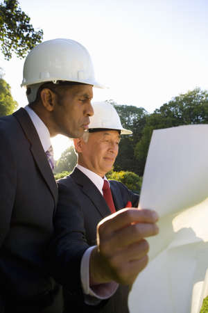 toils: Businessman and colleague in hardhats looking at blueprint, low angle view