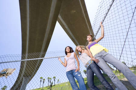 western european ethnicity: Small group of friends by fence beneath overpass, portrait, low angle view