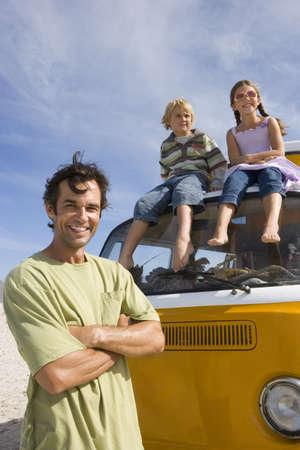 waistup: Hombre en la playa con los brazos cruzados por el hijo y la hija (5-9) en el techo de caravana, retrato, vista de �ngulo bajo