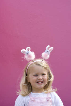 appreciating: Girl (2-4) wearing bunny rabbit headband by pink wall, smiling, portrait LANG_EVOIMAGES