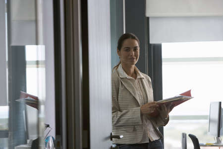 toils: Businesswoman standing in office, holding file, smiling, side view, portrait, doorway view